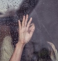Suicide is not the answer - Image of a depressed girl standing against a window