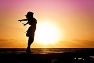 Suicide is not the answer - Image of a happy and free woman in the sunset